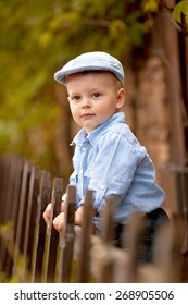 portrait of little boy in the blue shirt and  cap is standing near the wooden fence in the garden