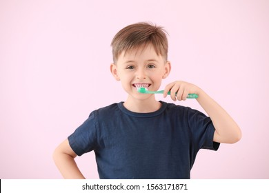 Portrait of little boy brushing teeth on color background