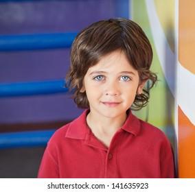 Portrait of little boy in casuals smiling in preschool