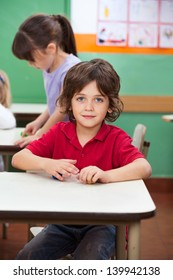 Portrait of little boy with clay while female friends playing in background at kindergarten