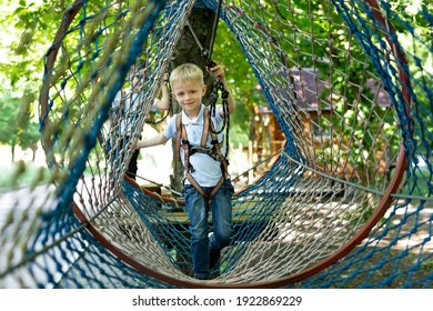 Portrait of a little boy in climbing gear in a rope park, holding a rope with a carbine.