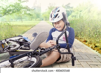 Portrait of little boy crying while holding his knee after falling from the bike at park