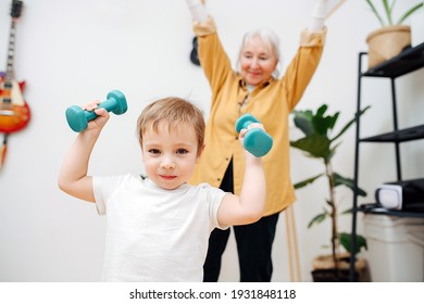 portrait of a little boy doing exercises with dumbbells in his hands against his grandmother's.