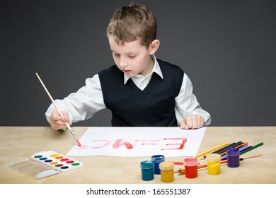 Portrait of little boy drawing energy formula with paints and pencils. Concept of arts and hobby