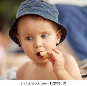 Portrait of little boy eating a cookie at the beach