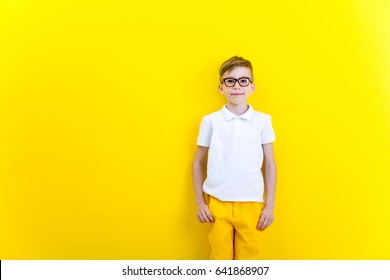 Portrait of a little boy with glasses on a yellow background