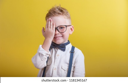 Portrait of little boy in glasses reviewing eyesight - vision testing concept. Kid closing one eye with hand. Happy smiling boy at the doctor ophthalmologist isolated on yellow background.