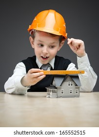 Portrait of little boy in hard hat with house model and ruler on grey background. Concept of real estate and engineering