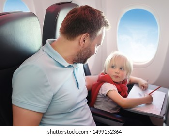 Portrait of little boy with his father during the flight by an airplane. Child painting picture.Traveling with kids.
