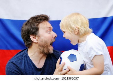 Portrait of little boy and his middle age father with russian flag on background. Fans child supporting and cheering their national team at the soccer/football sporting games