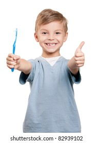 Portrait of a little boy holding a tooth brush over white background