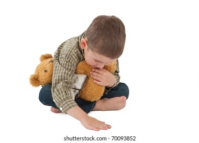 Portrait of little boy in jeans with toy bear isolated on white background