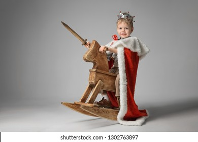 Portrait of a little boy in a knight costume on a rocking horse