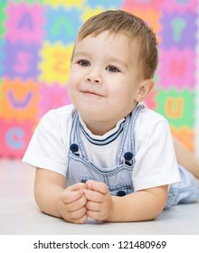 Portrait of a little boy laying on floor