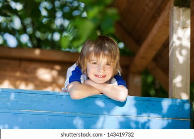 Portrait of little boy leaning on treehouse's wall at playground