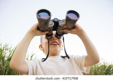 Portrait of little boy looking through binoculars on river bank. Cute kid with binoculars. The boy looks up at the sky through binoculars