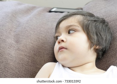 Portrait of little boy lying down on bean bag after finished playing games on his tablet, Toddler boy chilling out at home watching TV, Children playing at home concept