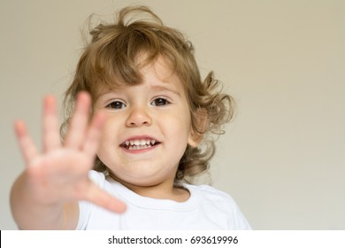 Portrait of a little boy making stop gesture on background, smiling and looking at camera, selective focus