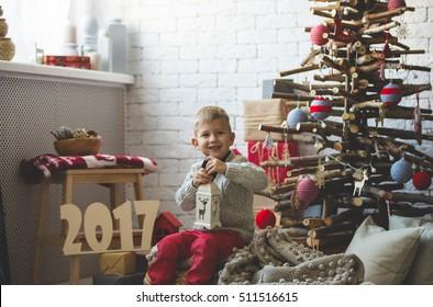 Portrait of little boy near fashion xmas tree