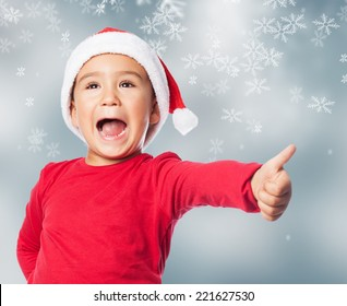 portrait of a little boy on christmas time with thumb up