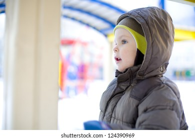 Portrait of the little boy at a playground in the winter