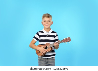 Portrait of little boy playing guitar on color background