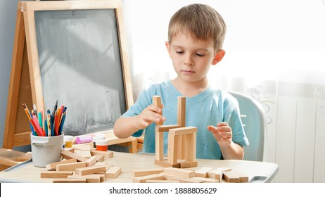 Portrait of little boy playing with wooden toy blocks and building tower from bricks. Concept of smart children and home education during lockdown and self isolation.