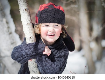 A portrait of a little boy with a red and black checkered hat. His hunting cap has furry ear flaps. The child is in preschool and posing outside for his head shot. He wears a blue sweater.