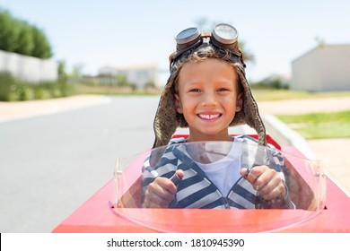 Portrait of little boy riding an handmade toy car on street with hands on steering wheel ready for the race. Smiling funny kid rides on a go-kart looking at camera with copy space outdoor.
