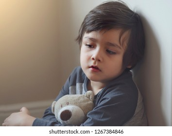Portrait of little boy with sad face holding teddy bear siting alone, Lonly child with botred face and look tired from illness, selective focus kid face with dry skin on cheek, - image
