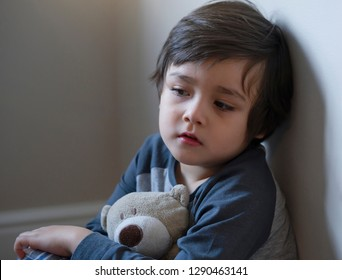 Portrait of little boy with sad face holding teddy bear siting alone in corner, Lonly child with bored face and look tired from illness, selective focus kid face with dry skin on cheek, - image