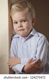 Portrait of little boy in shirt standing at the wall