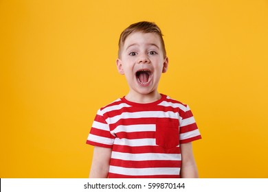Portrait of a little boy shouting isolated over orange background