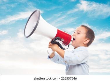 portrait of a little boy shouting on the megaphone