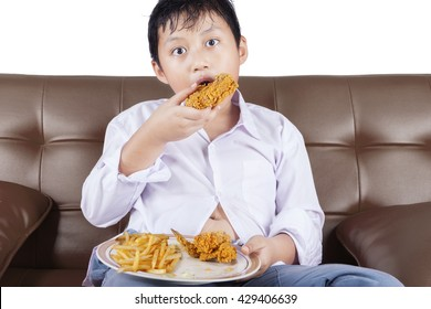 Portrait of a little boy sitting on the sofa while eating fried chicken and french fries