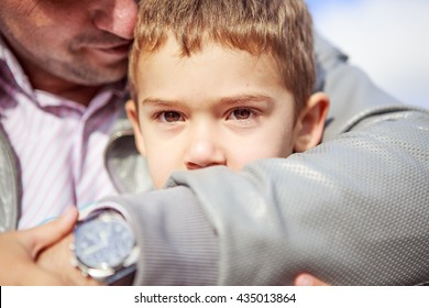 Portrait of little boy sitting on the bench next to his father