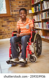 Portrait of little boy sitting in wheelchair at the library