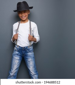 Portrait of a little boy smiling with black hat and suspenders on gray background