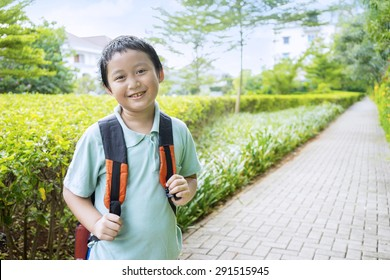Portrait of little boy smiling on the camera while carrying backpack, shot on the park