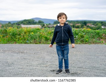 Portrait of little boy standing alone and looking out with thinking face with blurry background farm filed, 4-5 years old kid wearing hooded sweatshirt and blue jean posing on the field.
