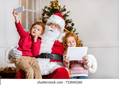 portrait of little boy taking selfie with santa claus while sister using tablet at home