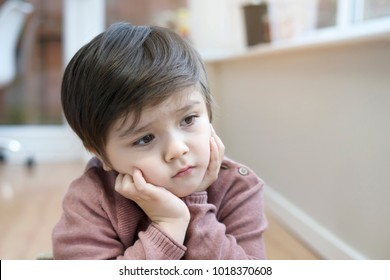 Portrait of little boy with upset face, Kid sad face sitting alone in the room, Unhappy child looking out, Spoiled children concept
