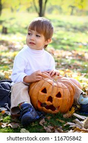 Portrait of a little boy who sitting on the ground in the woods with halloween pumpkin