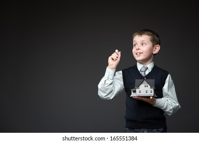 Portrait of little boy writing something with chalk and keeping home model on grey background