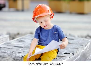 Portrait of little builder in hardhats reading construction drawing. Little boy`s dream concept