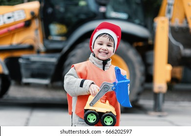 Portrait of little builder in hardhats working outdoors near Tractor excavator. Funny smiling child - engineer, construction worker or architect.