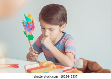 Portrait of little caucasian boy is coughing and playing toy or colorful wind turbine in living room at home. Education and Medical Concept.