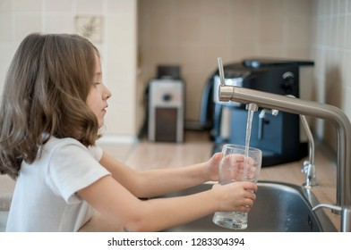 Portrait of a little caucasian girl gaining a glass of tap clean water. Kitchen faucet. Cute curly kid pouring fresh water from filter tap. Indoors. Healthy life concept - Shutterstock ID 1283304394