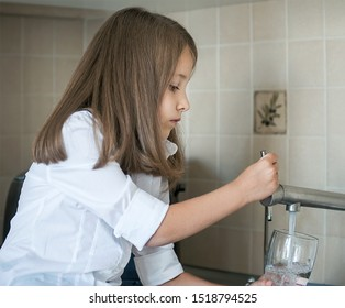 Portrait of a little caucasian girl gaining a glass of tap clean water. Kitchen faucet. Cute curly kid pouring fresh water from filter tap. Indoors. Healthy life concept