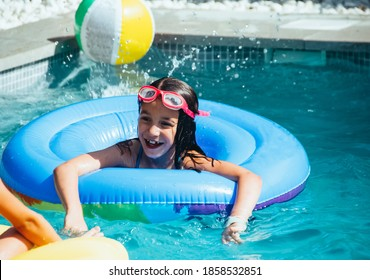Portrait of a little caucasian girl having fun in a pool with a floater